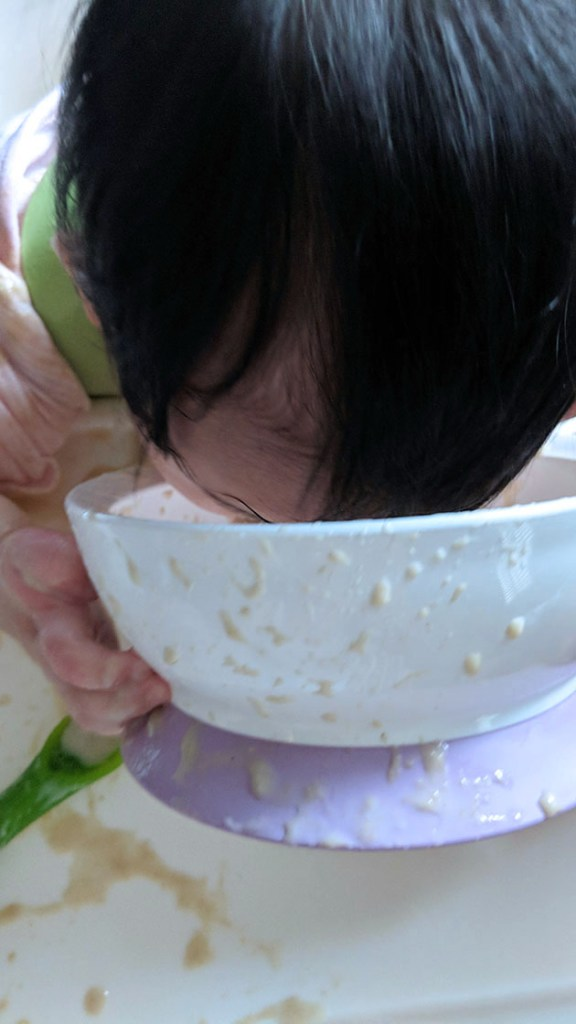 Baby leaning into bowl to eat cereal.