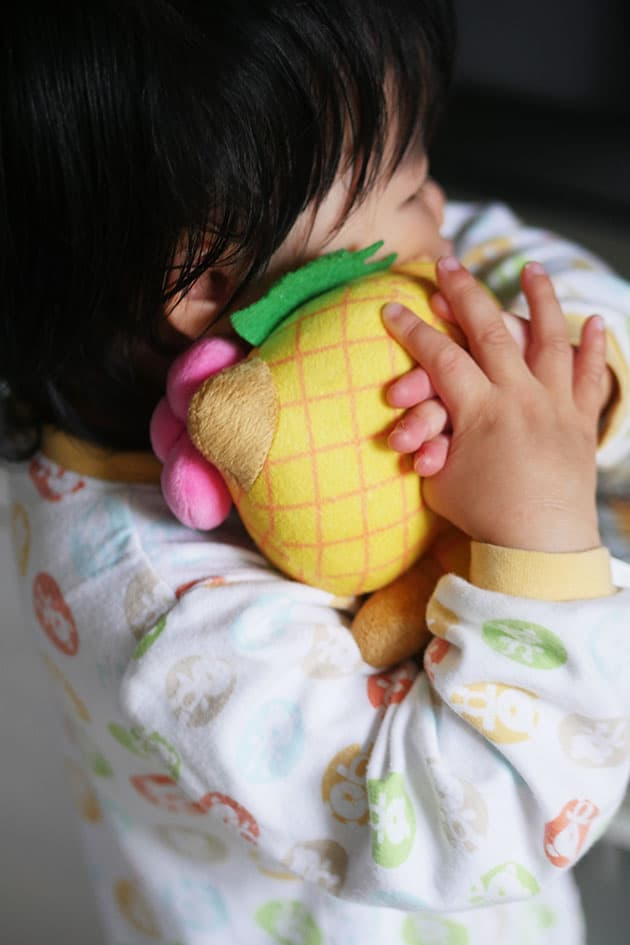 Baby hugging a stuffed animal before bedtime.