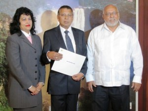 Justice Sukul [center] flanked by his wife [left] and President Donald Ramotar [right]