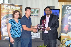 Squash player Benjamin Mekdeci who will represent Guyana at the upcoming US Open receives a decorative Guyana map from Minister of Tourism (ag) Irfaan Ali. Also in photo is Benjamin's mother, Dr. Kelly Mekdeci
