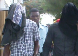 Collin Harris [left] and Kelvin Pollard [right] hides their faces as they leaves the Georgetown Magistrates' Court
