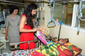 Lisa Ramotar spreads Christmas cheer with a gift to a child at the GPHC