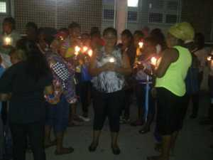 A grieving mother, Natalie Caseley (center) holds a candle at the vigil in front of the Georgetown Public Hospital. [iNews' Photo]
