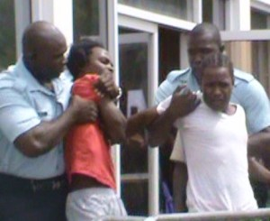 Charles Rollins and Trevor Barrow fight their way out of the Georgetown Magistrate's Court. [iNews' Photo]