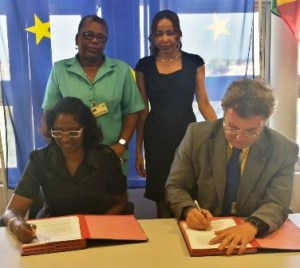 Ambassador Robert Kopecký [right] and Ms. Omattie Madray [left] sign the grant contract while Chantalle Haynes, [standing right] Director of Forward Guyana and Ann Greene [standing left] of the Child Protection Agency, Ministry of Human Services look on.