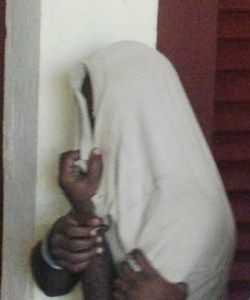 The accused hiding his face.