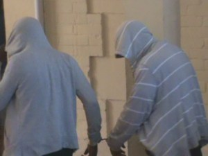 The two accused exiting the court room, as they hide their faces behind the hoodie. [iNews' Photo]