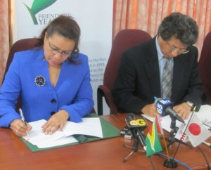 Guyana's Foreign Affairs Minister, Carolyn Rodrigues – Birkett and Japan's Ambassador to Guyana Yoshimasa Tezuka sign the agreement. [iNews' Photo]