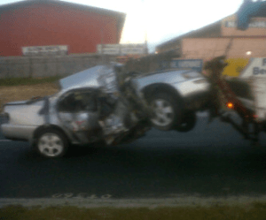 The mangled car being removed from the scene of the accident.