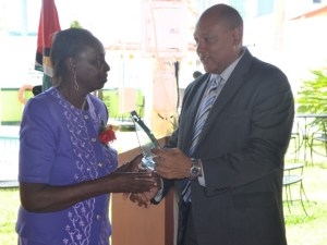 Speaker of the National Assembly Raphael Trotman presents an award to Shirley Edwards for 18 years of service.