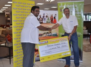 Minister of Tourism (ag) Irfaan Ali receives the cheque from Country Manager of Courts, Clyde de Haas