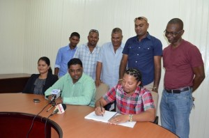 Minister of Housing and Water Irfaan Ali along with a section of the contractors looking on as one of the representatives signs the contract