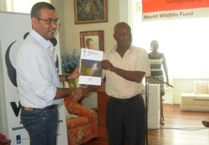 Minister Persaud receives the report from Country Manager WWF, Dr Patrick Williams. [iNews' Photo]