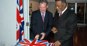Prime Minister, Samuel Hinds awaits his turn as British High Commissioner  Andrew Ayre has the first go at cutting the traditional birthday cake in celebration of Queen Elizabeth II's 88th birthday. [Guyana Chronicle Photo]