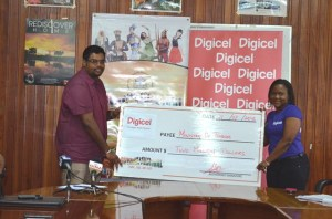Advertising and  Sales Manager, of Digicel Guyana, Alexis Longhorn handing over the $2M sponsorship cheque to Minister of Tourism (ag) Irfaan Ali for the inaugural Guyana Festival.