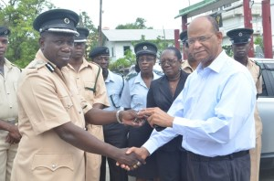Minister of Home Affairs Clement Rohee hands over the keys to the vehicles  to Deputy Director, Guyana Prison Service, Kyle Graham