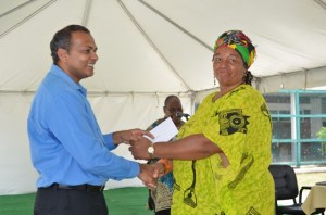 A member from one of the African Cultural groups receiving a cheque from Minister of Culture, Youth and Sport Dr. Frank Anthony.