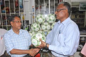 Chatram Persaud (left) hands over the footballs to Director of Sport Neil Kumar at the store's Robb Street location. [iNews' Photo]
