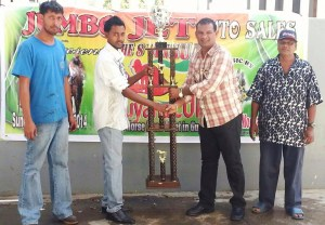 Member of the Tickaram family handing over the trophy to a representative of Jumbo Jet Auto Sales.