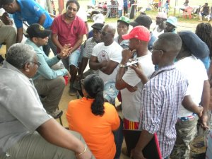 Minister of Natural Resources and the Environment Robert Persaud interacting with miners at Port Kaituma. [GINA Photo]