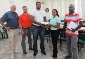 Senior Environmental Officer at EPA, Ms. Bibi Sharief (second from right) presenting Contracts to the Project Contractor, Mr. Alvin Chowramootoo (first from right), and IECS Representative, Mr. Deoraj Dalchand (centre) for Supervision of the Project.