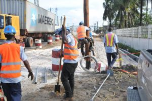 Workers of GT&T putting a new pole in the center of the carriageway, halting construction. [Photo provided by BK International]
