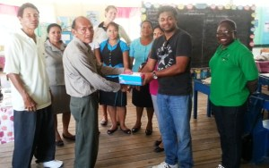Chief Executive Officer (ag) Deodat Indar along with CSR Officer Cassandra George-Mangru and Assistant Accountant Gaitrie Shivsankar handing over the footwear to the Headmaster John B