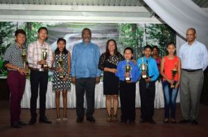 Prime Minister Samuel Hinds (center), Amerindian Affairs Minister Pauline Sukhai, and Home Affairs Minister Clement Rohee and top performing hinterland students, for Grade 6 and CSEC levels honoured by the ministry