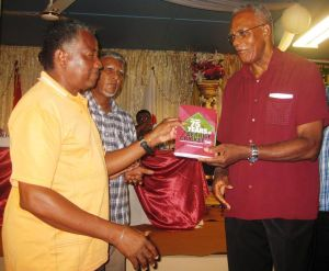 BCB President Keith Foster (left) receives a copy of one book from Mortimer George.