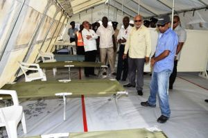 President Donald Ramotar accompanied by Health Minister Dr. Bheri Ramsaran and Public Works Minister Robeson Benn,  visiting one of the medical tents set up at the Cheddi Jagan International Airport. [GINA Photo]