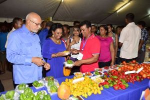 President Donald Ramotar and Mrs Yvonne Hinds  look at some local produce. [GINA Photo]