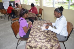 A parent completing the necessary paper work before uplifting her voucher at the Diamond Secondary School. [GINA Photo]