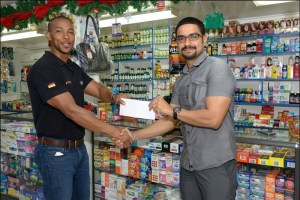 Managing Director of Medi-Care, Christopher Lowe presents the sponsorship to Onai Vasconcellos (left), Director of Advertising for Flex Night Inc.
