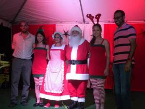 Mr. and Mrs. Clause and Santa Helpers are flaked by Mr. Damian Fernandes, Commissioner of the Protected Areas Commission (left) and Hon. Robert M. Persaud, Minister of Natural Resources and the Environment (right).