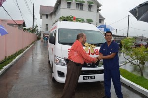 Minister of Health Dr. Bheri Ramsaran handing over the keys to the new ambulance at Director of the Accident and Emergency Department, Dr. Zulfikar Bux.