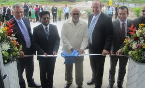 President Donald Ramotar flanked by Minister Ashni Singh and Qualfon Executives about to cut the ceremonial ribbon. [iNews' Photo]