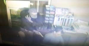 One of the gunmen pointing a gun to the receptionist demanding cash.