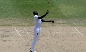 Jason Holder celebrates catching Ian Bell off his own bowling