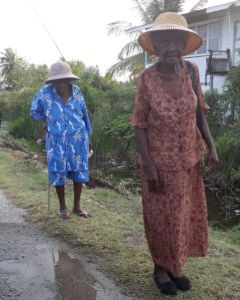 Two elderly women make their way to the polling station at Manchester Village, Corentyne. [iNews' Photo]
