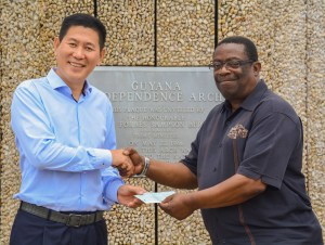Managing Director of Baishanlin, Chu Hongbo hands cheque over to Chief Coordinator, Larry London