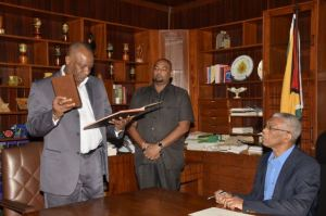 Mr. Joseph Harmon, Minister of State takes the oath of office as Secretary to the Defence Board before President David Granger