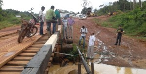 Ministers of Communities and Public Infrastructure, Ronald Bulkan and David Patterson along with engineers and Regional Officials inspecting an illegal connection and the pressure of the water