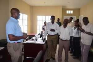 Minister Within the Ministry of Communities, Keith Scott engaging some of the workers at Winsor Estate