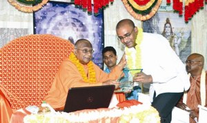 Swami Vidyananda  presents the Sangha Shield of Excellence to former President Bharrat Jagdeo in 2014. [Guyana Times Photo]