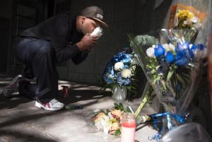 A man kisses a candle at a wreath laying site for the officer.