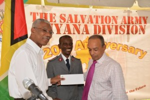 President David Granger handing over a cheque to Chairman of the Salvation Army's Advisory Board, Edward Boyer