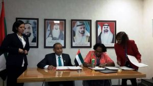 i.Minister Ferguson signing the agreement with an UAE official.