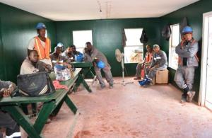 Workers listen to Minister Simona Broomes in their lunch room at Kurubuka mining site