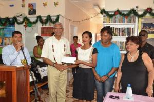 President David Granger presents a $2M cheque to Administrator of the Good Hope-Lusignan Learning Centre, Ms. Annette Roopchand