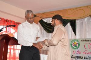 President David Granger handing over a donation to President of the Guyana Islamic Trust, Shaykh Abdul Aleem Rahim